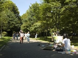 숲 한가운데서 그림을 그리는 시민의 모습