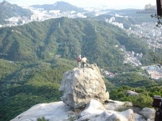북한산 족두리봉에 올라 도심의 풍경을 바라는 산행객들