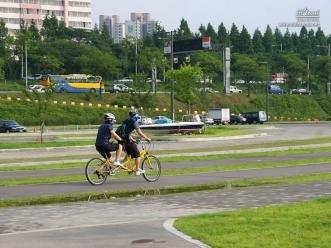 2인용 자전거를 즐기는 연인들의 다정한 모습