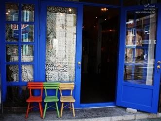 파란 외관에 나란한 원색 의자들로 꾸민 매장 외관