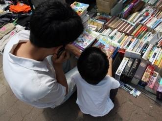 중고책 좌판 앞에서 책을 고르는 아버지와 아들